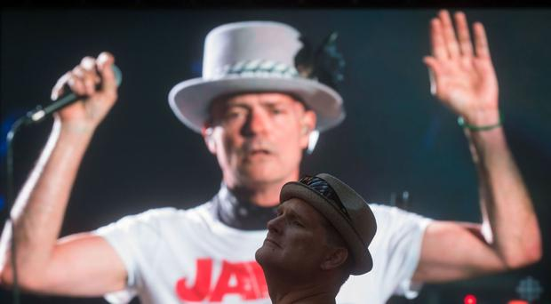 Lead singer of The Tragically Hip Gord Downie at his final gig, as a man watches at a viewing party in Vancouver (/The Canadian Press/AP)