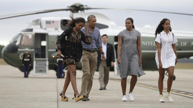 President Barack Obama with Michelle Obama and their daughters Malia, right, and Sasha, board Air Force One at Air Station Cape Cod (AP)