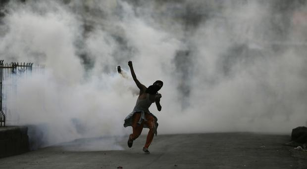 A Kashmiri protester throws a tear smoke shell (AP Photo/Mukhtar Khan)