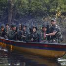 Rebels from the Revolutionary Armed Forces of Colombia patrol the Mecaya river in the southern jungles of Putumayo, Colombia (AP)