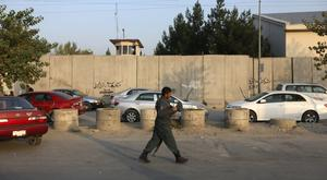 An Afghan security official walks past the American University of Afghanistan in Kabul after an attack in which 10 people were killed (AP)
