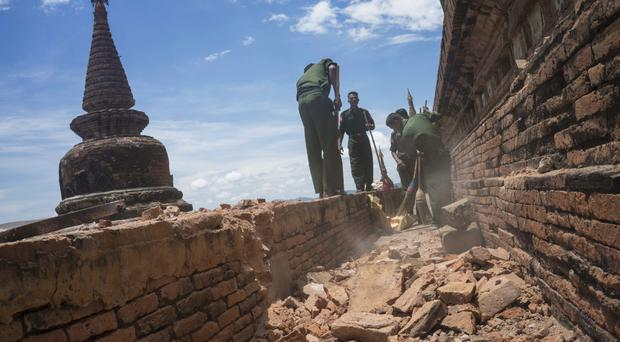 Military personnel clear debris at a temple that was damaged by a strong earthquake in Bagan, Burma (AP)
