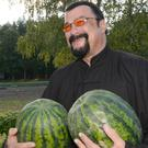 Steven Seagal holds two watermelons in the Belarus presidential residence of Drozdy, outside Minsk (AP)