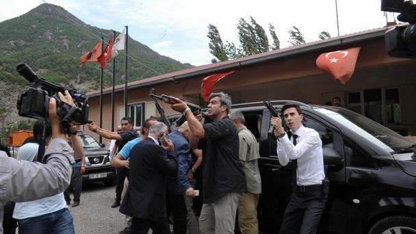 Bodyguards of Kemal Kilicdaroglu direct their guns towards a mountain as he gets into a car after an attack in Artvin, Turkey. (AP)