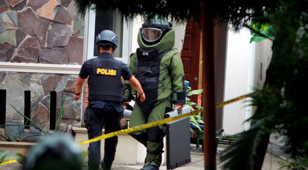 Bomb squad personnel carry an explosive from the Saint Joseph church