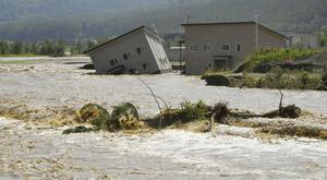 Floodwaters from the Sorachi river wash away a building after embankments of the river were broken on the northern island of Hokkaido (Kyodo News/AP)