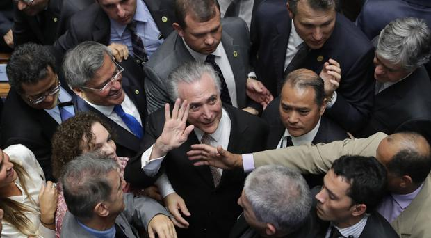 Michel Temer is surrounded by senators as he arrives to take the presidential oath at the National Congress in Brasilia (AP)
