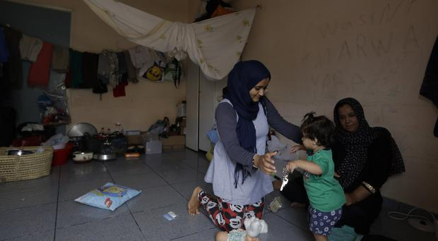 A woman with a child at an abandoned Greek hospital wing used as a shelter for refugees (AP Photo/Thanassis Stavrakis)