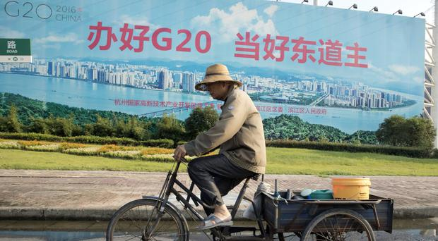 A man cycles past a propaganda board about the G20 in Hangzhou in eastern China's Zhejiang province (AP)