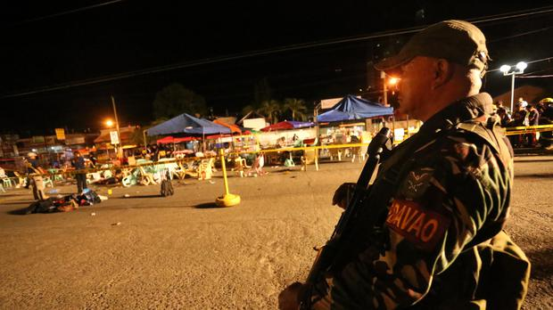 A Philippine soldier keeps watch at a blast site at a night market that southern Davao City (AP)