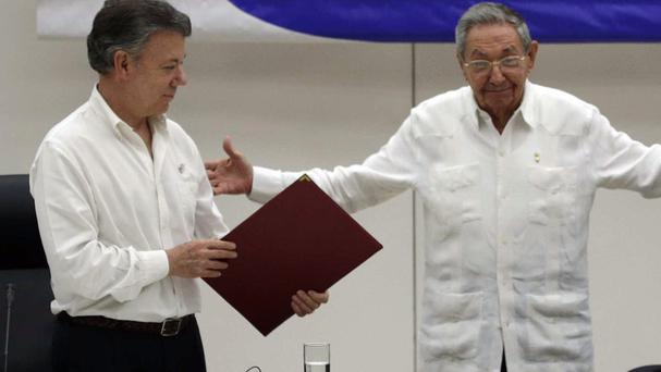 Colombian President Juan Manuel Santos with Cuba's President Raul Castro during a ceasefire signing ceremony in Havana in June (AP)