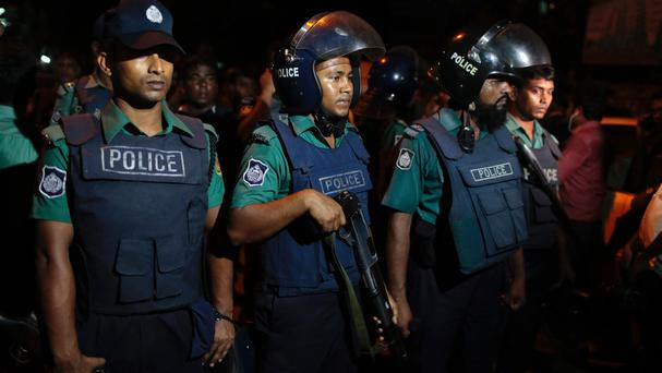 Bangladeshi policemen at the scene of a raid on a suspected militant hideout in Dhaka (AP)