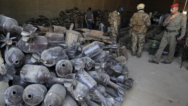 Iraqi security forces display home-made weapons and munitions formerly belonging to IS which were found in Fallujah (AP)