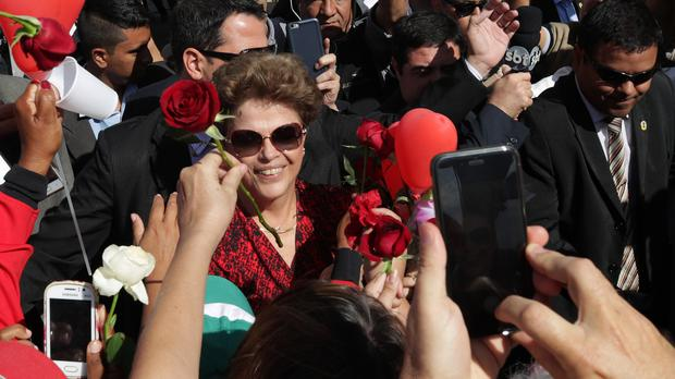 Dilma Rousseff receives flowers and gifts from supporters as she leaves the presidential residence (AP)