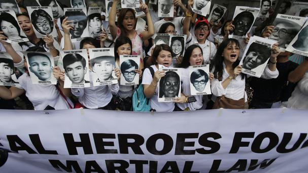 Anti-Marcos protesters hold pictures of victims of the martial law era in a rally outside the Philippines Supreme Court (AP)