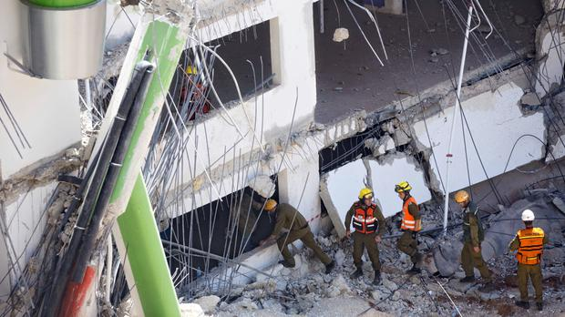 Israeli soldiers from the Home Front Command unit inspect the site of a collapsed multilevel underground parking in Tel Aviv (AP)