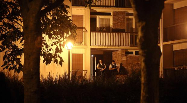 Police officers stand guard as they take part in a raid in Boussy-Saint-Antoine, east of Paris (AP)