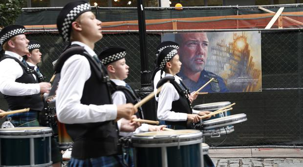 A marching band passes artwork depicting a fallen New York City police officer during the memorial procession (AP)