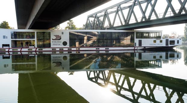 A river cruise ship sticks underneath a railway bridge on the Main-Danube Canal near Erlangen, Germany (Nicolas Armer/dpa/AP)