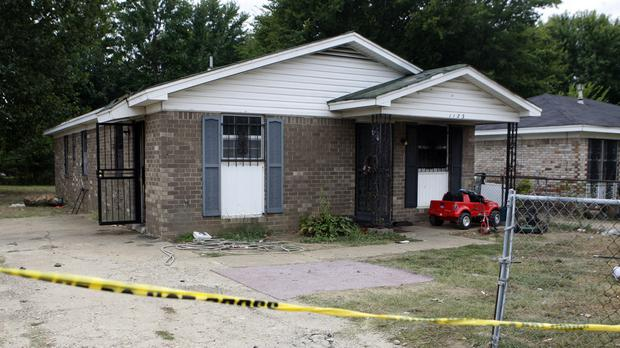 Security tape stretches across the driveway of a home where an early morning fire killed nine people in Memphis (AP)