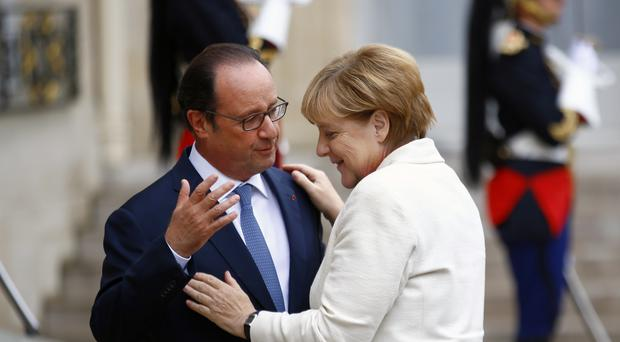 French president Francois Hollande, left, greets German chancellor Angela Merkel prior to their meeting at the Elysee Palace in Paris (AP)