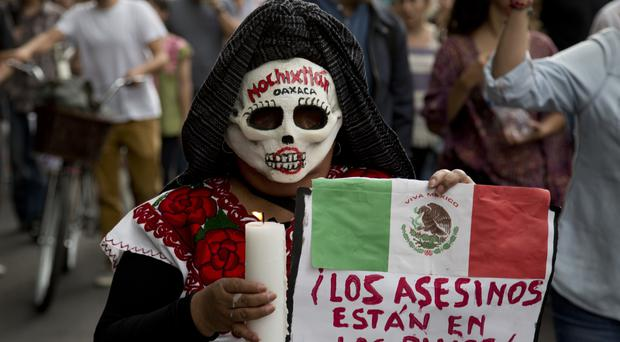 A masked woman at a march in Mexico City to demand the resignation of President Enrique Pena Nieto (AP)