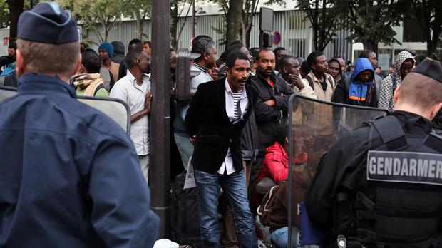 Migrants wait to be evacuated from a camp in the north of Paris (AP)