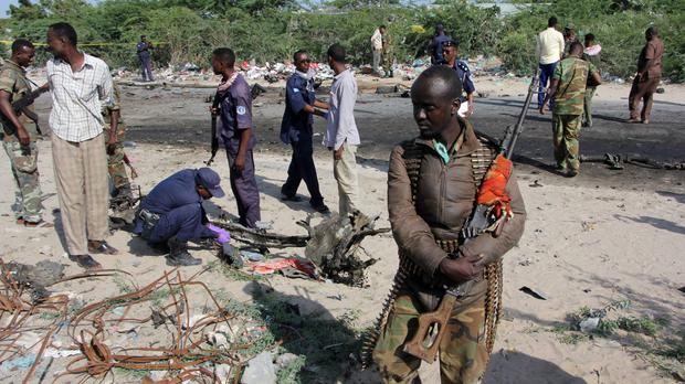 Somali soldiers stand near the wreckage of the car bomb (AP)