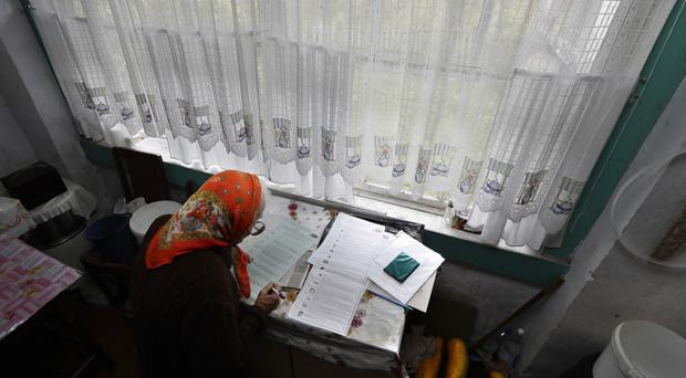 A woman reads her ballots papers in the village of Gusino, outside Smolensk (AP)