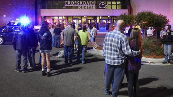 People stand near the entrance of the Crossroads Centre in St Cloud, Minnesota (Dave Schwarz/St Cloud Times via AP)