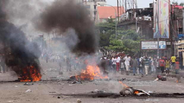 People stand near burning debris during election protests in Kinshasa (AP)