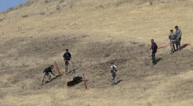 Authorities look over part of the wreckage of a US Air Force U-2 spy plane that crashed in the Sutter Butte mountains (AP)