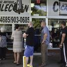 Customers stand in line at one of the few open cafes on Roosevelt Avenue, in San Juan, Puerto Rico (AP)