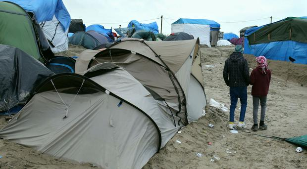 Orphaned refugee children walking amongst the shelters at the Jungle camp at Calais in France