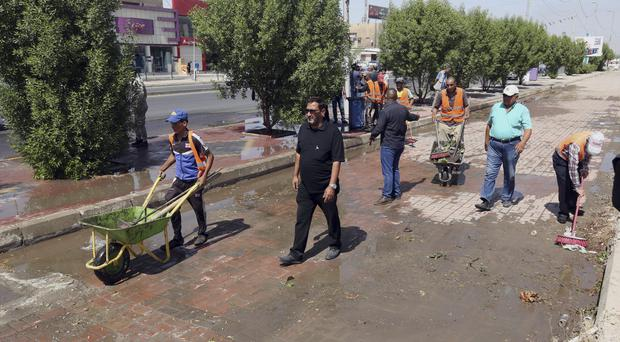 Iraqi municipality workers clean the scene of a suicide attack in Baghdad's western Eskan area (AP)