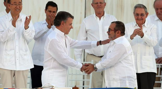 President Juan Manuel Santos and Rodrigo Londono shake hands after signing the peace agreement (AP)