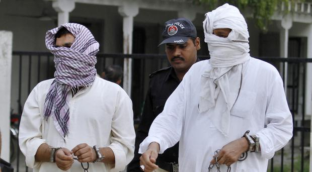 The ex-husband and the father of British woman Samia Shahid are escorted to court in Pakistan where they face trial for murder over her alleged honour killing (AP)