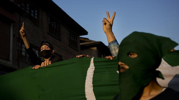 Kashmiri protesters holding a Pakistan occupied Kashmir flag during a demo in Srinagar (AP)