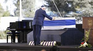 Israel's president Reuven Rivlin at the coffin of former president Shimon Peres at the Mount Herzel national cemetery in Jerusalem (AP)