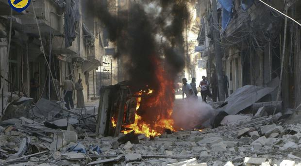 Syrians watch a burning car among damaged buildings after air strikes in Aleppo (White Helmets/AP)
