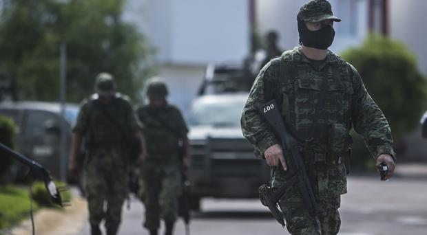 Soldiers patrol after a military convoy was ambushed with grenades and high-powered guns, killing five soldiers in the city of Culiacan (AP)
