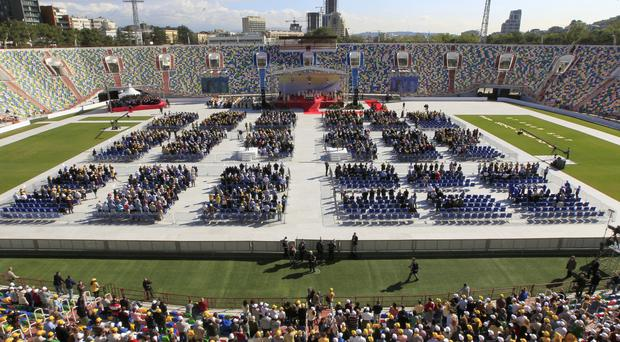 Pope Francis, sitting under a canopy, celebrates Mass in Tbilisi's stadium (AP)
