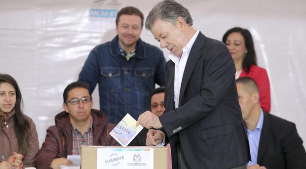 President Juan Manuel Santos votes in a referendum to decide whether or not to support the peace deal he signed with Farc (AP)