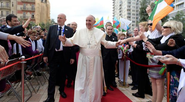 Pope Francis is cheered by the faithful as he arrives at Baku's Church of the Immaculate, Azerbaijan
