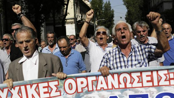 Pensioners chant slogans as they take part in an anti-austerity protest against pension cuts in Athens (AP)