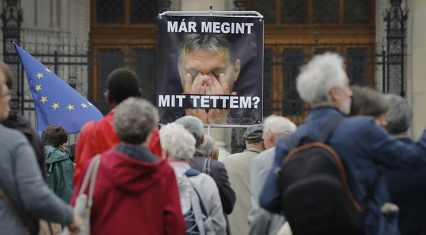 A man holds a poster with the image of Hungarian premier Viktor Orban that reads 'What have I done again?' (AP)