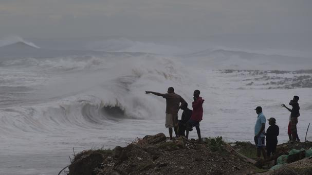 People watch the surf produced by Hurricane Matthew on the outskirts of Kingston, Jamaica (AP)
