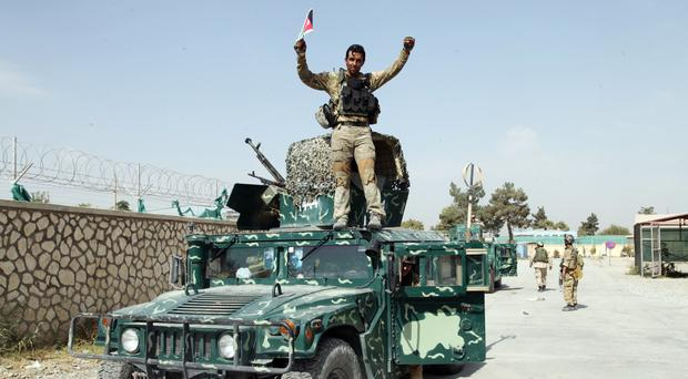An Afghan soldier raises his hands as a victory sign, in Kunduz city, where fierce gun battles with the Taliban are under way for a second day (AP)