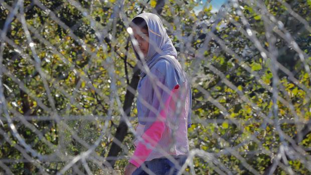 A migrant girl walks behind a barbed wire fence at a makeshift camp in Horgos, Serbia, seen from the Hungarian side of the border (AP)