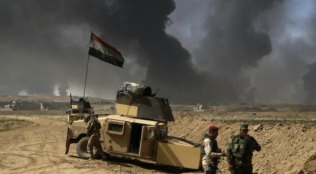 Iraqi soldiers stand on the frontline outside the town of Qayyarah as smoke rises from burning oil fields (AP)